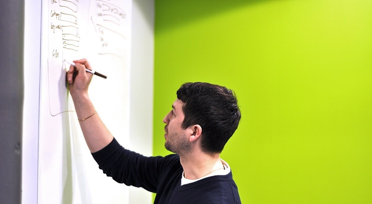 man writing on a whiteboard about the latest development in digital marketing